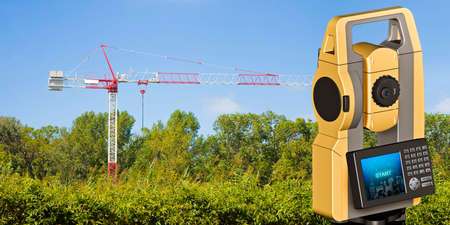 Red and white tower crane surrounded by nature and 3D rendering of a geodesic device, called Total Station, used for the survey of topographic maps and topographical survey - concept image with a cadastral map on foreground. Reklamní fotografie