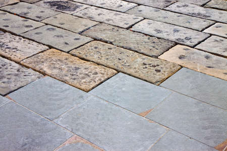 Restoratione of an old stone paving with new carved paving made with gray stone blocks in an italian pedestrian zone