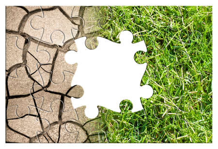 Cracked ground and green meadow - climate change concept in jigsaw puzzle shape.