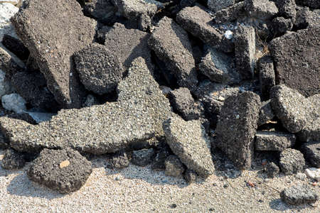 Cracked asphalt pieces after demolition of a road surface in a construction site for renovation ready to be recycled. Banco de Imagens