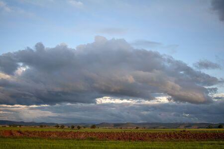 field landscape with clouds in the sky