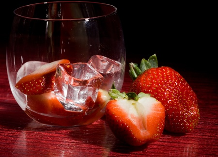 photo of strawberries on ice on red table photo