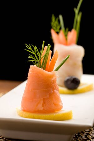 photo fo delicious  smoked salmon rolls with tomatoes inside photo