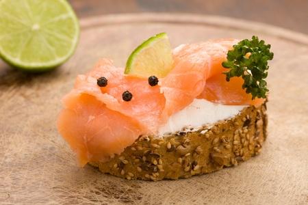 スモーク サーモンとおいしいカリカリ穀物パンの写真