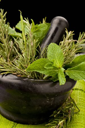 photo of fresh aromatic herbs in a mortar on glass table with black background Stock Photo - 8947044