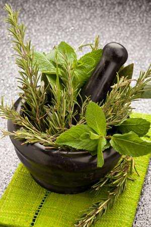 Photo des herbes aromatiques fraîches dans un mortier sur la table de verre avec fond noir