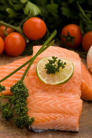 photo of delicious salmon filet with lime and parsley on chopping board with vegetables arround photo