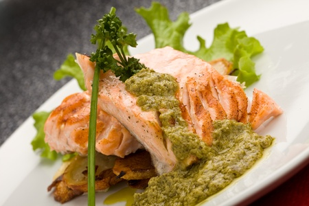 pesto: photo of delicious grilled salmon with green basil sauce and vegetables