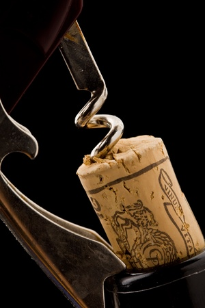 weinverkostung: Foto des Flaschen�ffner auf schwarzem Hintergrund ziehen ein Cork au�erhalb der Flasche Lizenzfreie Bilder
