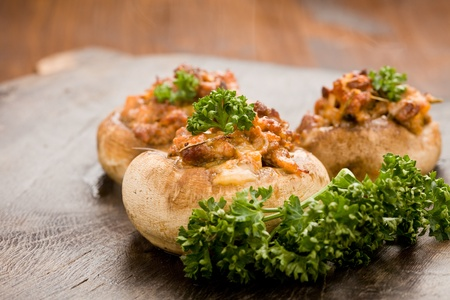 champignons: photo of delicious stuffed mushrooms with meat on wood table with parsley on it Stock Photo