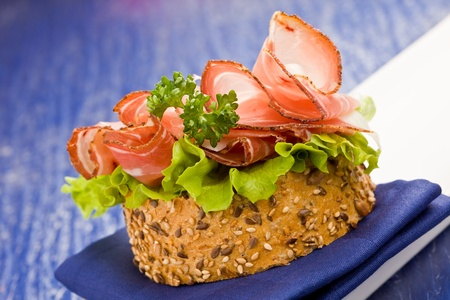 Delicious bacon and salad sandwich on blue cloth with parsley Stock Photo - 9009289