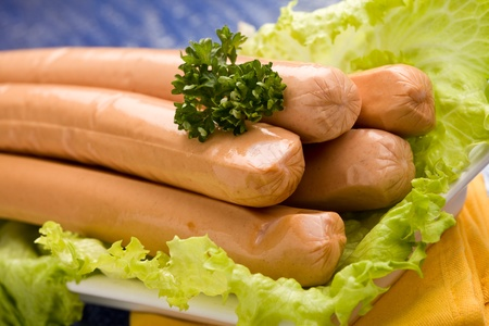 photo of delicious german sausages on green fresh lettuce with parsley