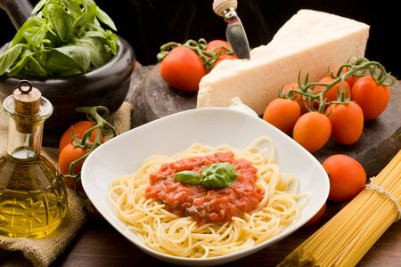 meal preparation: photo of italian spaghetti with tomatoe sauce and their ingredients arround Stock Photo