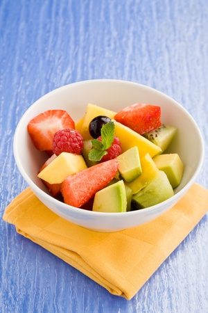 fruit salad: photo of colorful fruit salad on blue glass table with small mint leaf Stock Photo