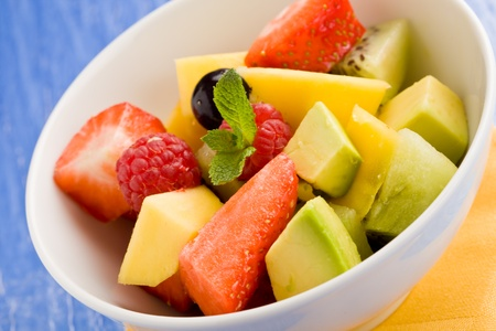 photo of colorful fruit salad on blue glass table with small mint leaf Stock Photo