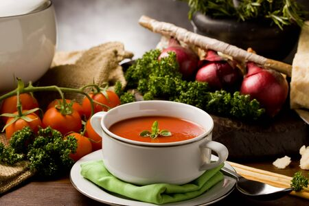 rustic food: photo ofo delicious tomato soup with vegetables on wooden table