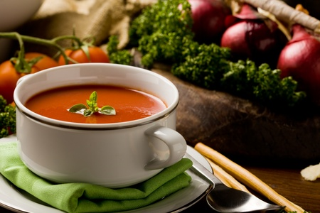 soup bowl: photo ofo delicious tomato soup with vegetables on wooden table