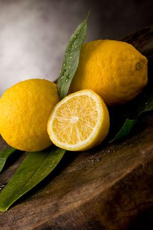 citricos: foto de limones frescos de amarillos con hojas y gotas de agua sobre la mesa de madera Foto de archivo
