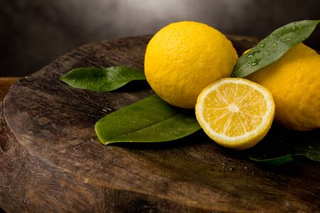photo of fresh yellow lemons with leaves and water drops on wooden table photo
