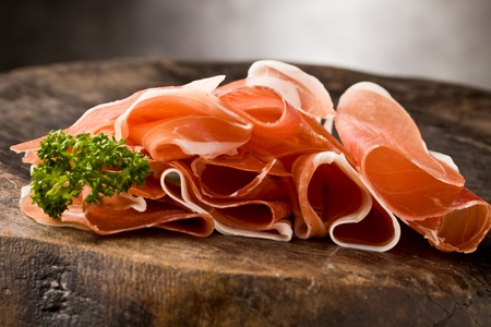 raw ham: photo of delicious sliced bacon on wooden table with parsley Stock Photo