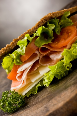 photo of delicious sandwich with smoked bacon and cheese on wooden table