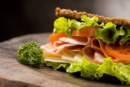 ham sandwich: photo of delicious sandwich with smoked bacon and cheese on wooden table