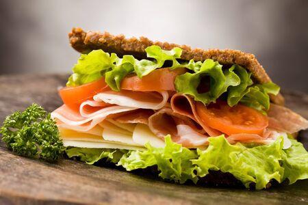 alimentos saludables: foto de delicioso bocadillo con tocino ahumado y queso en mesa de madera Foto de archivo