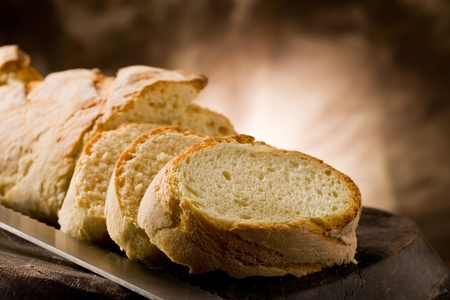 photo of delicious sliced bread on wooden table with knife photo
