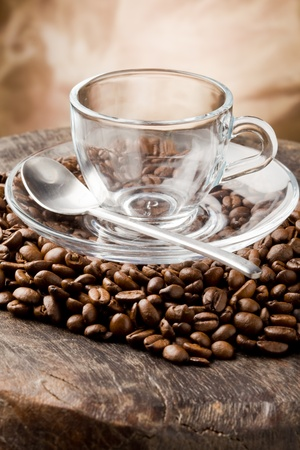 photo of empty glass cup on coffee beans over wooden table Stock Photo