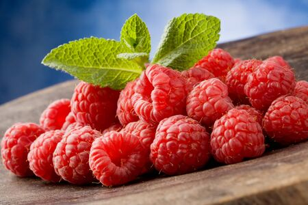 photo of delicious red raspberries with mint leaves on wooden table Stock Photo - 9194424