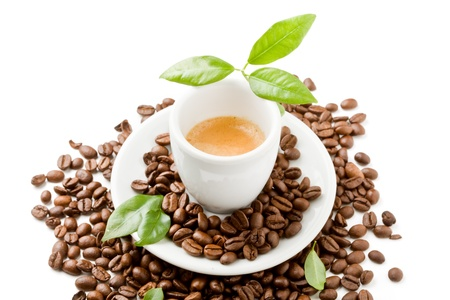 photo of espresso cup over coffee beans with green leaves on white isolated background photo