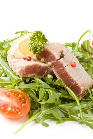 photo of sliced Tuna Steak with arugula salad  on white isolated background Stock Photo - 9194437