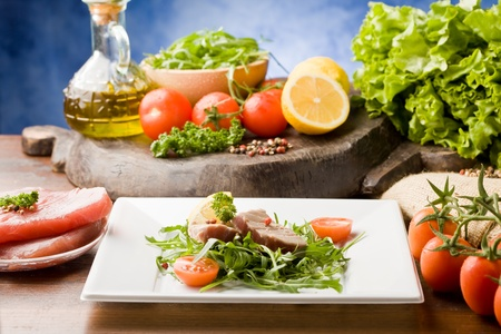 photo of sliced Tuna Steak with arugula salad and ingredients arround Stock Photo