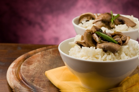 vegetarian food: photo of delicious risotto with mushrooms on wooden table