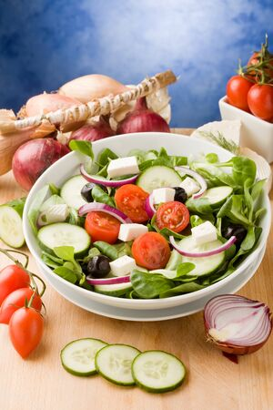 photo of delicious greek salad on wooden table in front of blue background with spot light photo