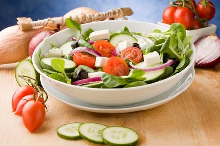 finocchio: Foto di deliziosa insalata greca sul tavolo di legno di fronte a sfondo blu con luce spot Archivio Fotografico