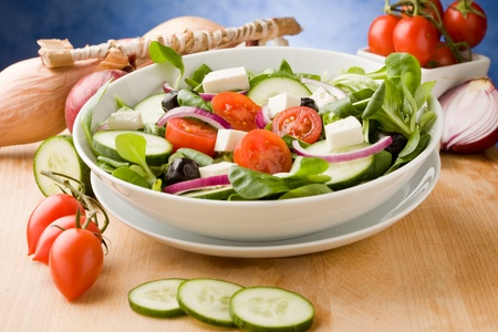 photo of delicious greek salad on wooden table in front of blue background with spot light