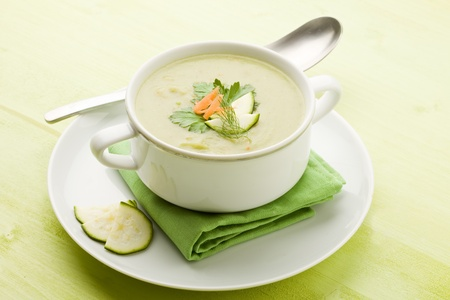 zucchini: photo of vegetarian vegetable soup on green wooden table with different vegetables arround Stock Photo