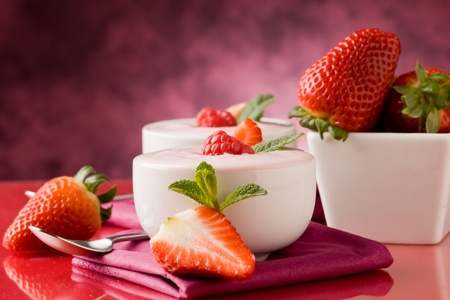 photo of delicious strawberry yogurt on red glass table photo