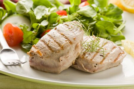 photo of grilled tuna steak with sald on green wooden table Stock Photo