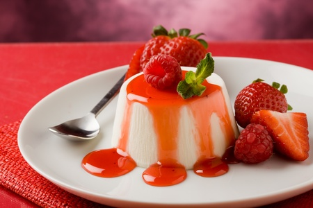 cotta: photo of italian panna cotta dessert with strawberry sirup and mint leaf Stock Photo
