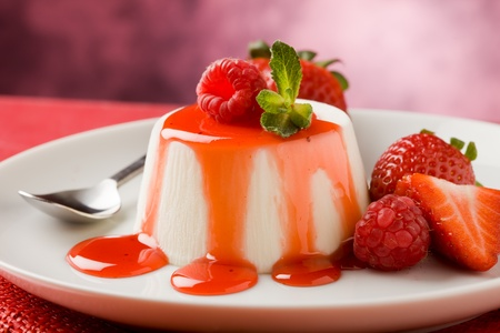 Foto van Italiaanse panna cotta dessert met aardbei siroop en muntblad