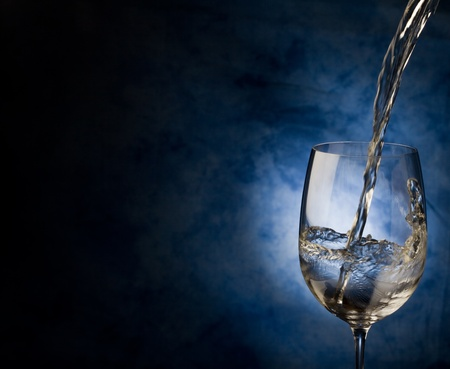 Photo of white wine inside a wine glass with abstract background photo
