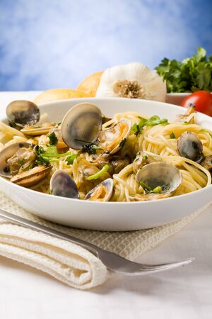photo of delicious pasta with clams in front of a blue background photo