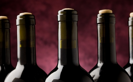 photo of five wine bottles in front of violet background photo