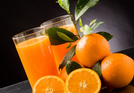 photo of fresh orange juice with water drops and green leaves