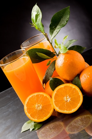 photo of fresh orange juice with water drops and green leaves photo