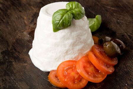 ricotta cheese: photo of delicious ricotta cheese with tomatoes on wooden table with basil