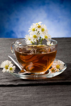 photo of delicious chamomile tea with marguerite reflecting on the tea photo