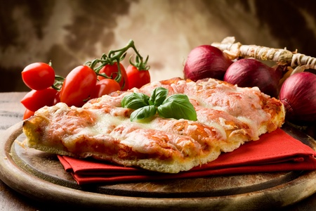 zwiebeln: Foto des K�stliches St�ck Pizza mit Basilikumblatt darauf